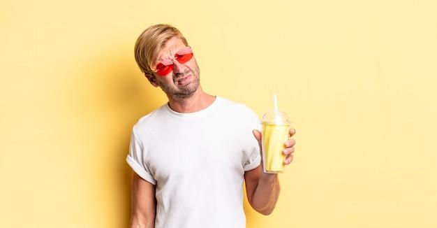 Blonde volwassen man die zich verward en verward voelt met een milkshake