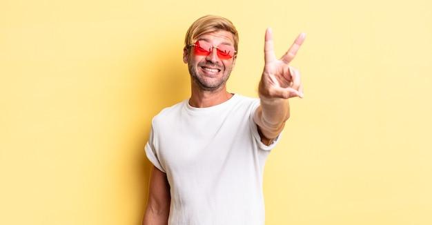 Blonde volwassen man lacht en ziet er gelukkig uit, gebaart overwinning of vrede en draagt een zonnebril