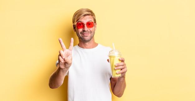 Blonde volwassen man lacht en ziet er gelukkig uit, gebaart overwinning of vrede met een milkshake
