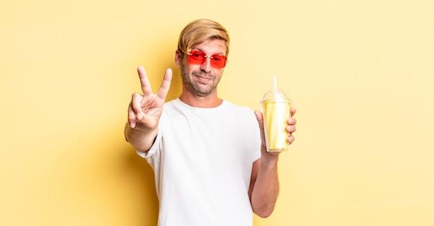 Blonde volwassen man lacht en ziet er vriendelijk uit, nummer twee tonend met een milkshake