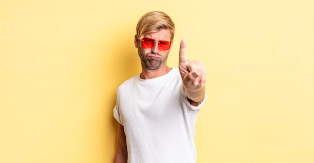 Blonde volwassen man lacht en ziet er vriendelijk uit, toont nummer één en draagt een zonnebril