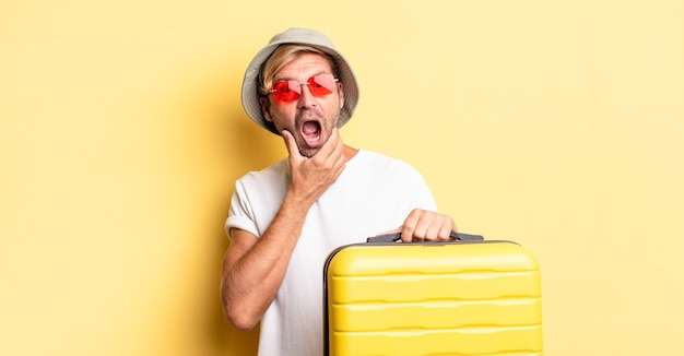 Blonde volwassen man met mond en ogen wijd open en hand op kin. reiziger concept