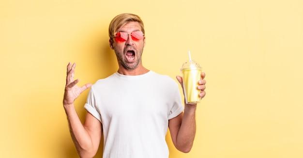 Blonde volwassen man schreeuwen met handen in de lucht met een milkshake