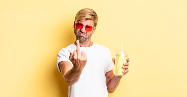 Blonde volwassen man voelt zich boos, geïrriteerd, opstandig en agressief met een milkshake