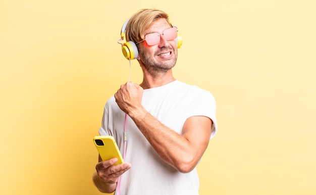 Blonde volwassen man voelt zich gelukkig en staat voor een uitdaging of viert feest met een koptelefoon