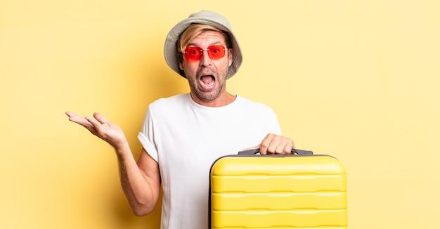 Blonde volwassen man voelt zich gelukkig en verbaasd over iets ongelooflijks. reiziger concept