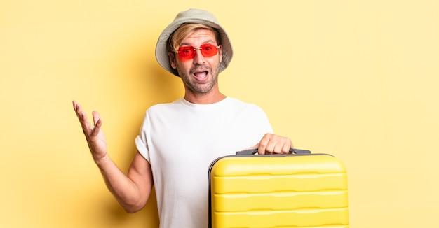 Blonde volwassen man voelt zich gelukkig, verrast en realiseert een oplossing of idee. reiziger concept