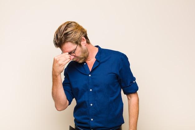 Blonde volwassen man voelt zich gestrest, ongelukkig en gefrustreerd, raakt voorhoofd aan en lijdt aan migraine of ernstige hoofdpijn