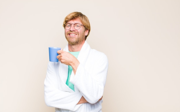 Blonde volwassen mens die een badjas en een bril draagt en een koffiekop houdt