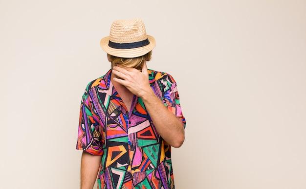 Blonde volwassen reizigersmens die gestrest, beschaamd of overstuur kijkt, met hoofdpijn, gezicht bedekt met hand