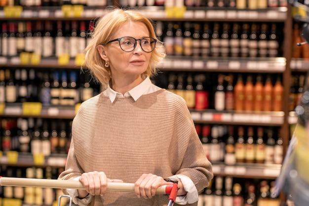 Blonde volwassen vrouwelijke klant in vrijetijdskleding winkelwagentje duwen tijdens het wandelen langs de planken met drankjes in de supermarkt