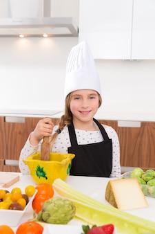 Blonde vriendelijke meisje junior chef-kok op aanrecht