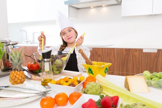 Blonde vriendelijke meisjes ondergeschikte chef-kok op countertop salade