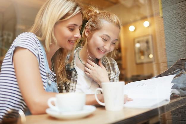 Blonde vriendinnen zitten in café