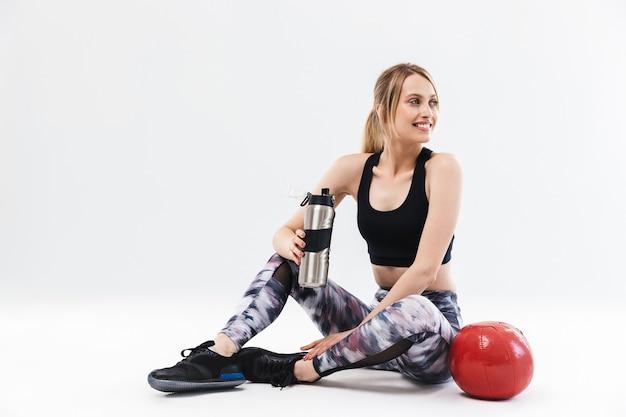 Blonde vrouw 20s gekleed in sportkleding uit te werken en oefeningen te doen met fitness bal tijdens aerobics geïsoleerd over witte muur