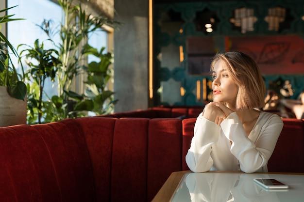 Blonde vrouw alleen in cafe