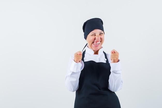 Blonde vrouw balde vuisten, tong uitsteekt in zwarte kok uniform en ziet er mooi uit. vooraanzicht.