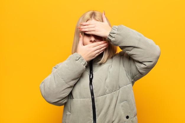 Blonde vrouw bedekt gezicht met beide handen nee zeggen tegen de camera! afbeeldingen weigeren of foto's verbieden
