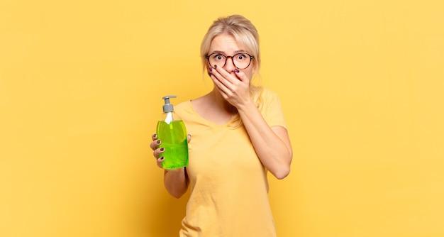 Blonde vrouw bedekt mond met handen met een geschokte, verbaasde uitdrukking, houdt een geheim of zegt oeps saying