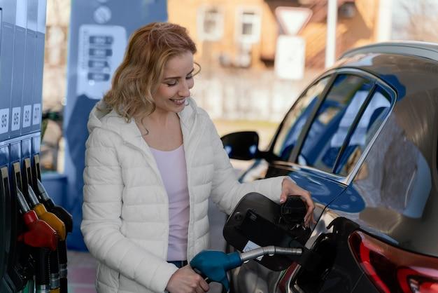 Blonde vrouw bij het benzinestation met haar auto