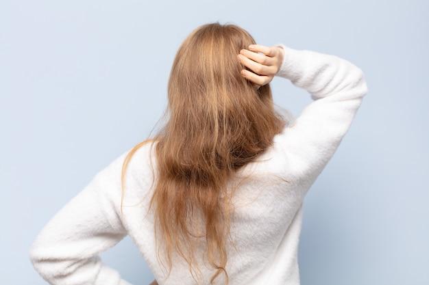 Blonde vrouw denkt of twijfelt, krabt aan haar hoofd, voelt zich verward en verward, achter- of achteraanzicht