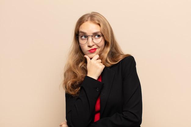 Blonde vrouw denkt, voelt zich twijfelachtig en verward, met verschillende opties, zich afvragend welke beslissing ze moet nemen