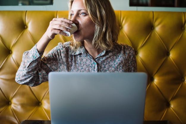 Blonde vrouw die aan haar laptop bij een koffie werkt