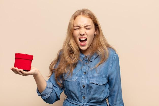 Blonde vrouw die agressief schreeuwt, erg boos, gefrustreerd, verontwaardigd of geïrriteerd kijkt en nee schreeuwt