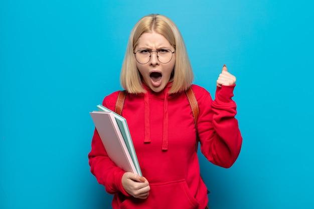 Blonde vrouw die agressief schreeuwt met een boze uitdrukking of met gebalde vuisten om succes te vieren