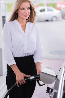 Blonde vrouw die auto middelgroot schot van brandstof voorziet
