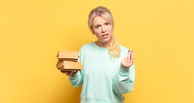 Blonde vrouw die capice of geldgebaar maakt en u vertelt uw schulden te betalen!