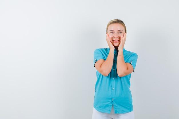 Blonde vrouw die de handen op de wangen houdt in blauwe blouse geïsoleerd