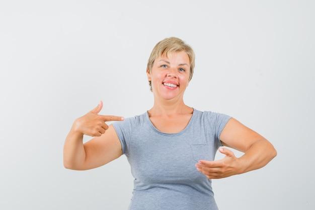 Blonde vrouw die doet alsof ze iets bij de hand houdt, wijst ernaar in een lichtblauw t-shirt en kijkt uitgeput. vooraanzicht.