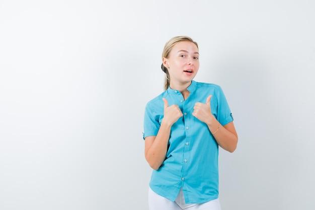 Blonde vrouw die dubbele duimen in blauwe blouse toont en er gelukkig uitziet