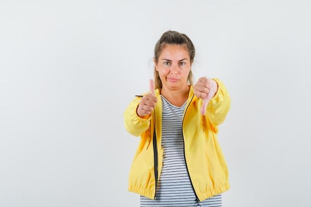 Blonde vrouw die duim op en neer toont terwijl grimassen in geel bomberjack en gestreept overhemd en peinzend kijken