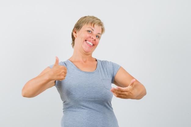 Blonde vrouw die duim toont en doet alsof ze iets bij haar hand houdt in een lichtblauw t-shirt en er vrolijk uitziet. vooraanzicht.
