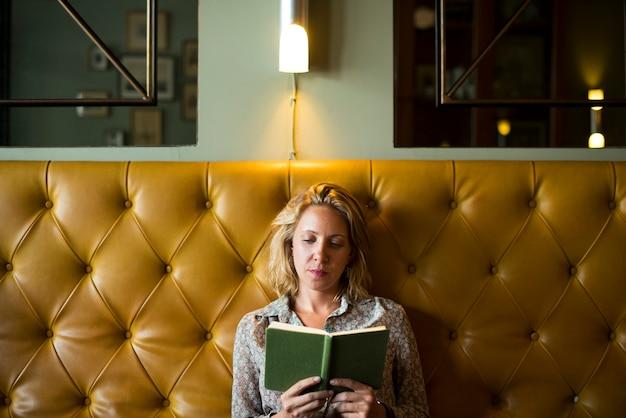 Blonde vrouw die een boek leest