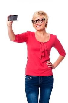 Blonde vrouw die een bril draagt die zelfportretfoto neemt