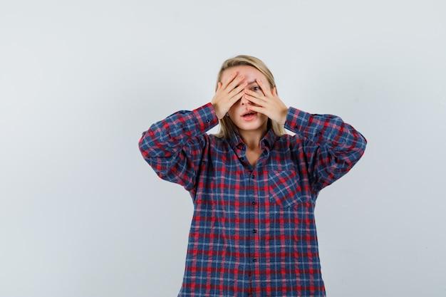 Blonde vrouw die een deel van het gezicht bedekt met handen en door vingers in geruit overhemd kijkt en gefocust, vooraanzicht kijkt.