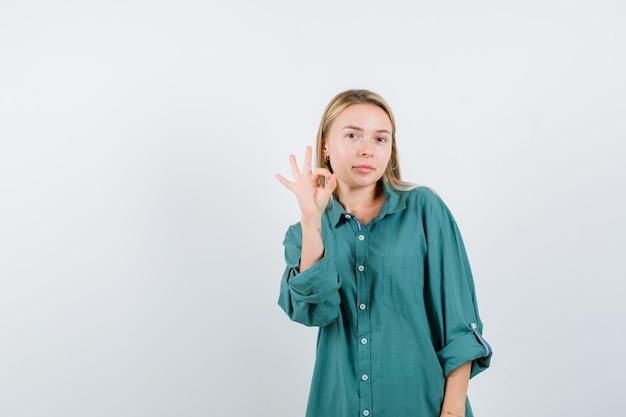 Blonde vrouw die een goed gebaar in een groen shirt toont en er zelfverzekerd uitziet