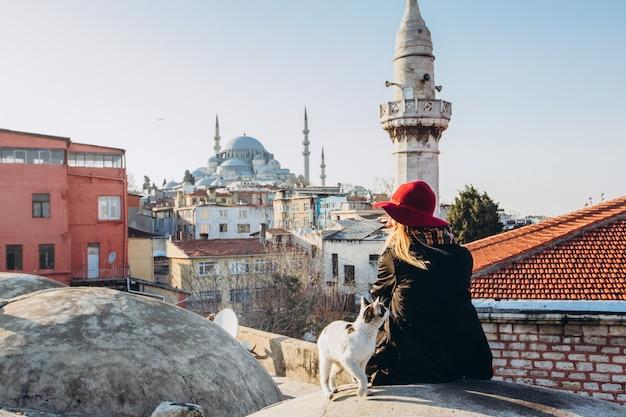Blonde vrouw die een kat op het dak strijken met het oog op de moskee, istanboel, turkije. meisje in een hoed zit op het dak in istanbul, zonnige herfstdag. het reizigersmeisje loopt door de winter istanboel.