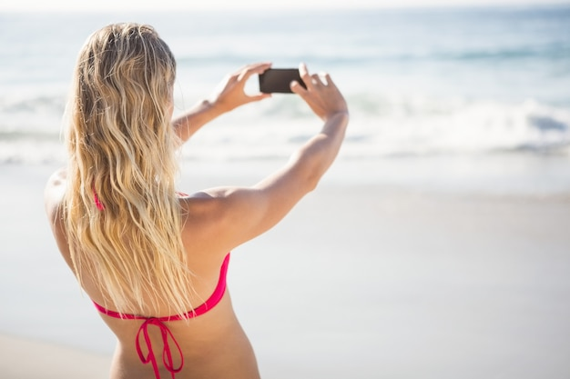 Blonde vrouw die een selfie neemt
