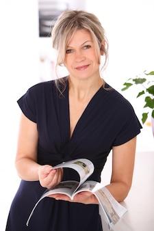Blonde vrouw die een tijdschrift leest