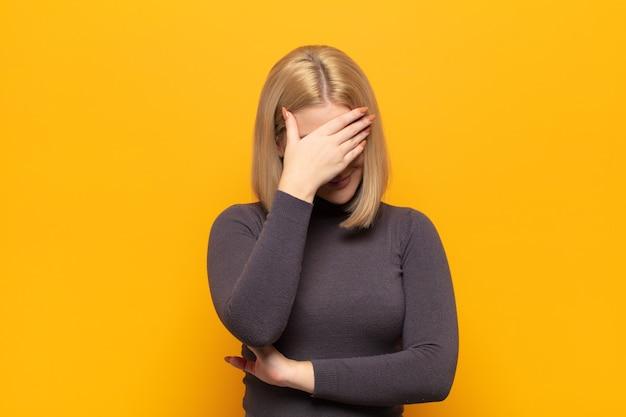 Blonde vrouw die er gestrest, beschaamd of overstuur uitziet, met hoofdpijn, gezicht bedekt met hand