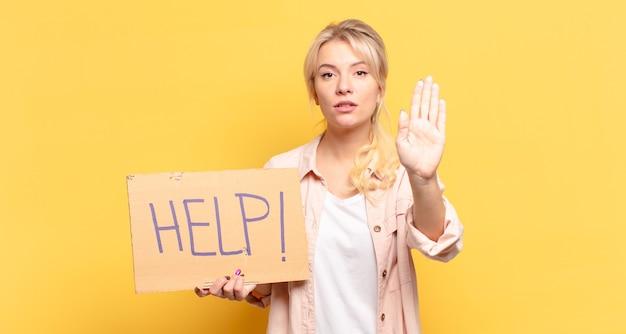 Blonde vrouw die er serieus, streng, ontevreden en boos uitziet met een open palm die een stopgebaar maakt