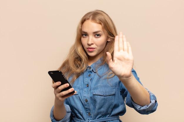 Blonde vrouw die ernstig, streng, ontevreden en boos kijkt die open palm toont die stopgebaar maakt
