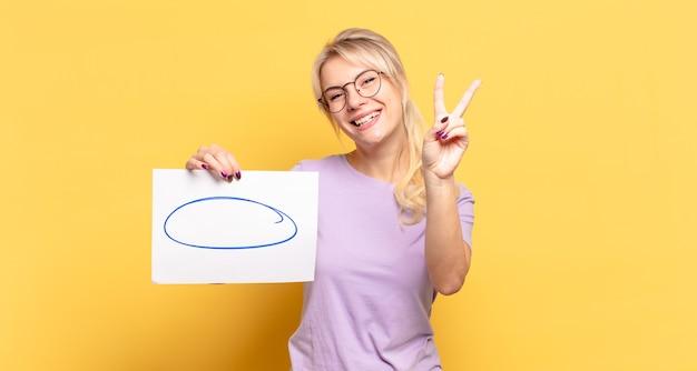 Blonde vrouw die gelukkig, zorgeloos en positief glimlacht en kijkt, overwinning of vrede met één hand gebaart