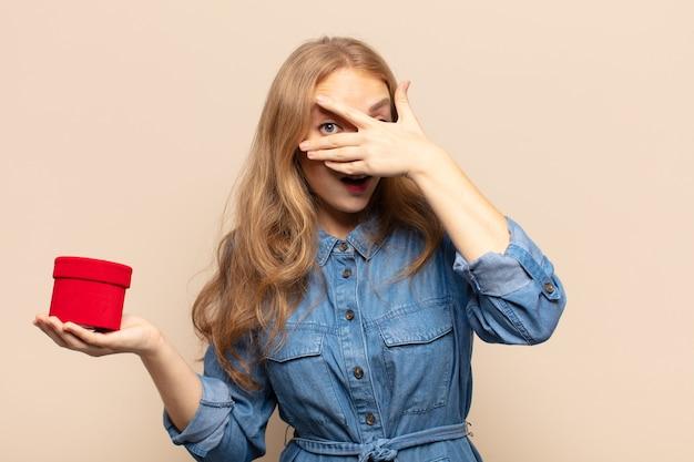 Blonde vrouw die geschokt, bang of doodsbang kijkt, gezicht bedekt met hand en tussen vingers gluurt