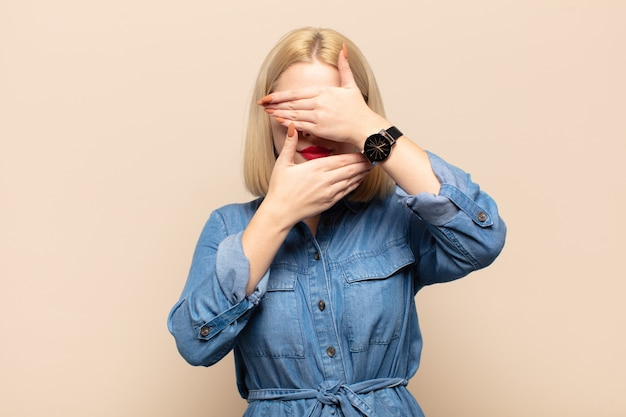Blonde vrouw die gezicht bedekt met beide handen en nee zegt tegen de camera! afbeeldingen weigeren of foto's verbieden