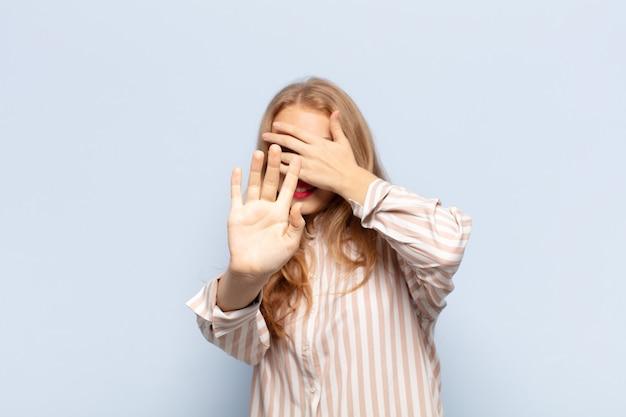 Blonde vrouw die gezicht bedekt met hand en andere hand naar voren zet om de camera te stoppen, foto's of afbeeldingen weigeren